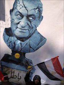 """An Egyptian girl waves a national flag beneath a picture of a cracked bust of Egypt's President Hosni Mubarak with Arabic writing below reading """"invalid"""", Cairo, Egypt, 11 February 2011"""