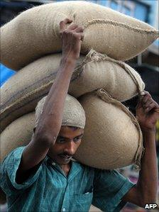 A labourer carries sacks of food grains in India