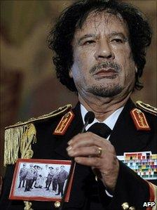 Col Gaddafi wears a picture depicting the execution of Omar al-Mukhtar in Rome in 2009