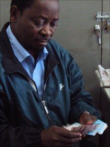 A man counts Mozambican meticais