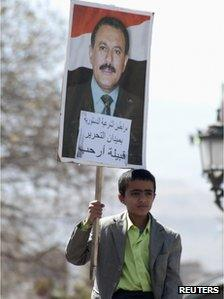 A boy carries a poster with a picture of outgoing Yemeni President Ali Abdullah Saleh while attending weekly Friday prayers, during a rally to show support for Saleh, in Sanaa January 20, 2012