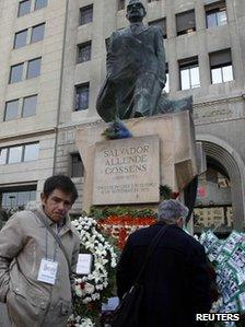 Flowers are left at a statue of Salvador Allende