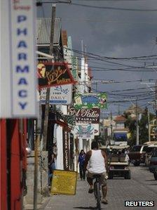 A man rides his bicycle past stores by the main square in San Pedro November 15