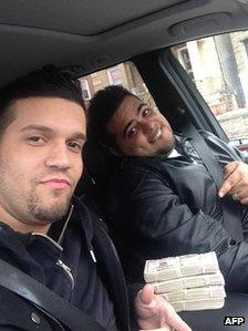 This photo obtained on 10 May 10 2013, by the US Attorney's Office in New York shows defendants Elvis Rafael Rodriguez (left) and Emir Yasser Yeje as they pose on 25 March 2013 with what Federal prosecutors said was stolen money