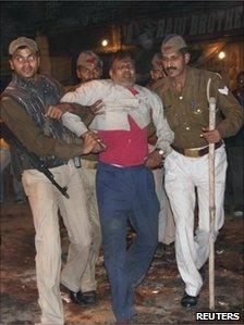 An injured man is helped from the scene of the explosion (7 December 2010)