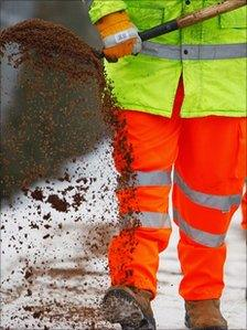 A council worker spreading road salt