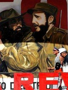 Tourists walk past a painting depicting guerrilla leader Camilo Cienfuegos and Fidel Castro in Havana on 29 December 2008