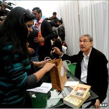 Turkish author and Nobel laureate Orhan Pamuk (R) signs books at the Jaipur Literature Festival, India, 21 January 2011