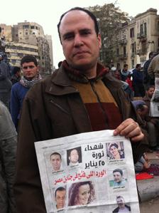 Protesters holding newspaper report about dead demonstrators