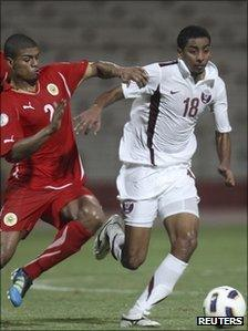 Qatar's Mohammed el-Sayed (white kit) fights for the ball with Bahrain's Mohammed Hussain