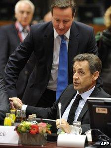 UK Prime Minister David Cameron stands behind French President Nicolas Sarkozy at the Brussels summit, 26 October