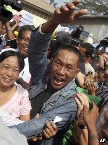 A Myanmar political prisoner waves in jubilation as he is released from Insein prison in Rangoon, Burma, on Friday