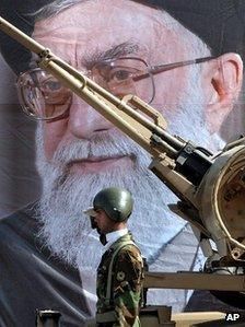 An Iranian army soldier salutes in front of a picture of the Supreme Leader, Ayatollah Ali Khamenei (2005)