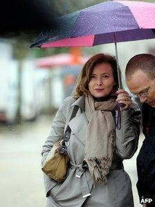 Valerie Trierweiler (L), companion of the President of the Correze Council General Assembly Francois Hollande, stands under an umbrella during a visit at the marketplace on April 21, 2012 in Tulle, southwestern France