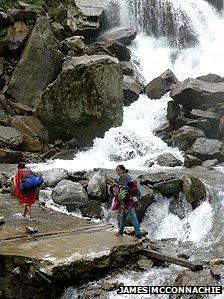 Two people walk alongside a waterfall