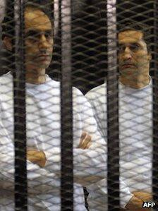 Alaa (R) and Gamal Mubarak stand inside a cage in a courtroom during their verdict hearing in Cairo on June 2 2012