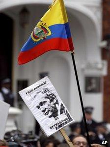 Supporters of Julian Assange hold up a placard and the flag of Ecuador outside the Ecuadorean Embassy in London