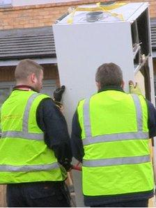 Builders removing the heating system on a housing estate in Runcorn.