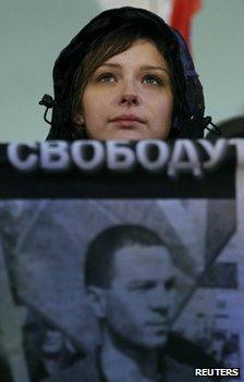 A protester holds a placard with a photo of Vladimir Akimenkov in Moscow, 30 October
