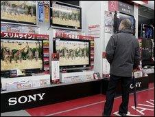 A customer checks Japanese electronics giant Sony's Bravia brand LCD TVs at an electronics shop in Tokyo