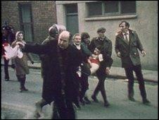 Father Daly waves a bloodstained handkerchief as he tries to lead one of the victims of Bloody Sunday, Jackie Duddy, to safety