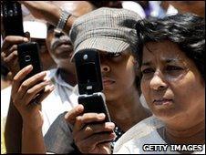 People take photos on their mobiles
