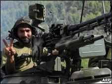 Pakistani soldier in tank making victory salute