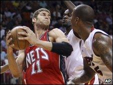 Miami Heat's players apply pressure on New Jersey Nets' Brook Lopez