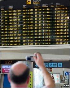 A passenger takes a photograph of a departure board displaying cancelled flights at Bilbao's airport in Loiu, northern Spain, on May 8, 2010.