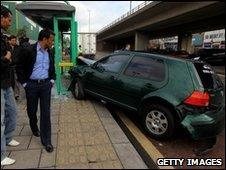 People gather at the scene of a car crash at a bus shelter next to where Gordon Brown and his cabinet were launching a poster campaign on April 30, 2010 in Birmingham,