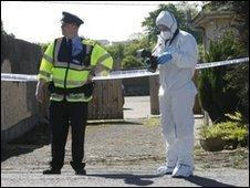 Garda officer and forensic officer at the scene of the bomb find