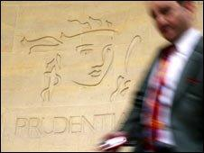 Man walking past a Prudential sign