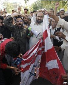 Pakistani Muslims burn flags during an anti-Facebook demonstration