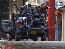 Jamaican police patrol a market area near the Tivoli Gardens