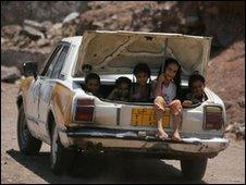 Children sit in the boot of a car in Yemen