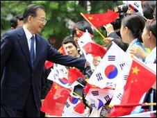 Chinese Premier Wen Jiabao (L) is greeted by children waving Chinese and South Korean flags (29 May)
