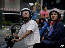 A couple look up at the ruins of Bangkok's Central World Plaza shopping mall on 22 May 2010