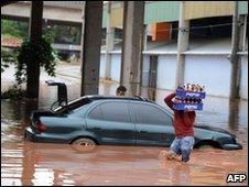 Man carries bottles through flood in Guatemala