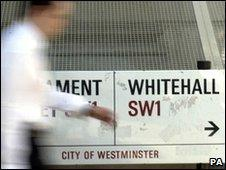 Man passes Whitehall street sign