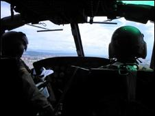Anti-narcotics officers in a helicopter on a reconnaissance mission
