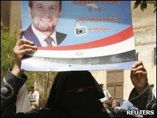 A supporter of the Muslim Brotherhood holds a candidates placard (1 June 2010)