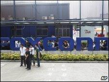 Staff gather at the company sign outside Foxconn's plant in Shenzhen on 26 May 2010