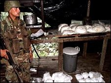A soldier guards cocaine in a drug lab in Colombia