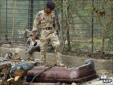 An Iraqi soldier inspects the scene of a car bomb explosion in Baghdad