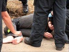Police restrain a young woman outside the camp