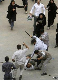 Iranian plainclothes policemen beat an election protester in Tehran, 14 June 2009