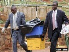 Police detectives with boxes of evidence from blast site