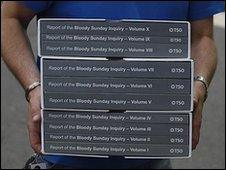A person carries a copy of the Saville Inquiry report