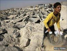 A Palestinian labourer collects gravel at abandoned airport in Rafah