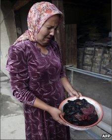 An ethnic Uzbek woman cries over the blood-stained clothing of her 25-year-old sister, who was eight months pregnant when she was shot and killed by a sniper in Jalalabad, 16 June, 2010.